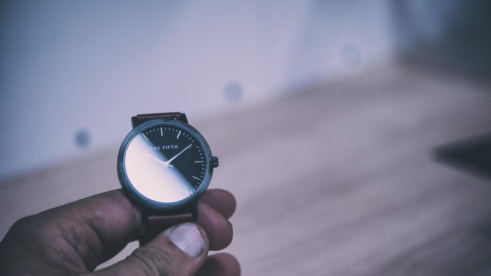 腕時計を手に持っている