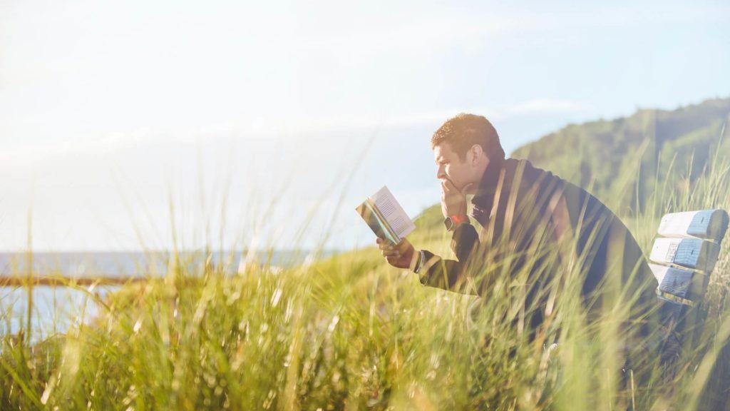 男性が外で本を読んでいる