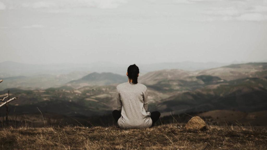 女性が荒野で1人きりで座っている
